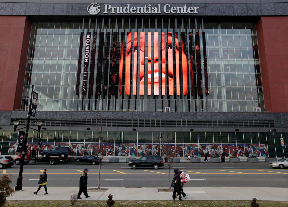 . People walk past, a large image of Whitney Houston displayed on the side of the Prudential Center in Newark, N.J., Tuesday, Feb. 14, 2012. Houston\'s funeral will be held Saturday in the church where she first showcased her singing talents as a child, her family choosing to remember her in a private service rather than in a large event at an arena. Officials had discussed the possibility of holding a memorial at the Prudential Center, a major sports and entertainment venue that can seat about 18,000 people, but the funeral home said it had been ruled out. Houston, 48, died Feb. 11 at a hotel in Beverly Hills, Calif., just hours before she was set to perform at producer Clive Davis\' pre-Grammy Awards bash. Whitney Houston was Google\'s number one most searched trending person and overall search term of 2012. (AP Photo/Mel Evans)