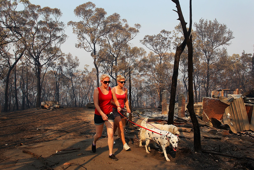 . Melissa White assists her sister Christie Daschke at her home destroyed by bushfire on October 21, 2013 in Winmalee, Australia. One man has died and hundreds of properties have been destroyed in bush fires that are devastating the Blue Mountains and Central Coast regions of New South Wales.  (Photo by Lisa Maree Williams/Getty Images)