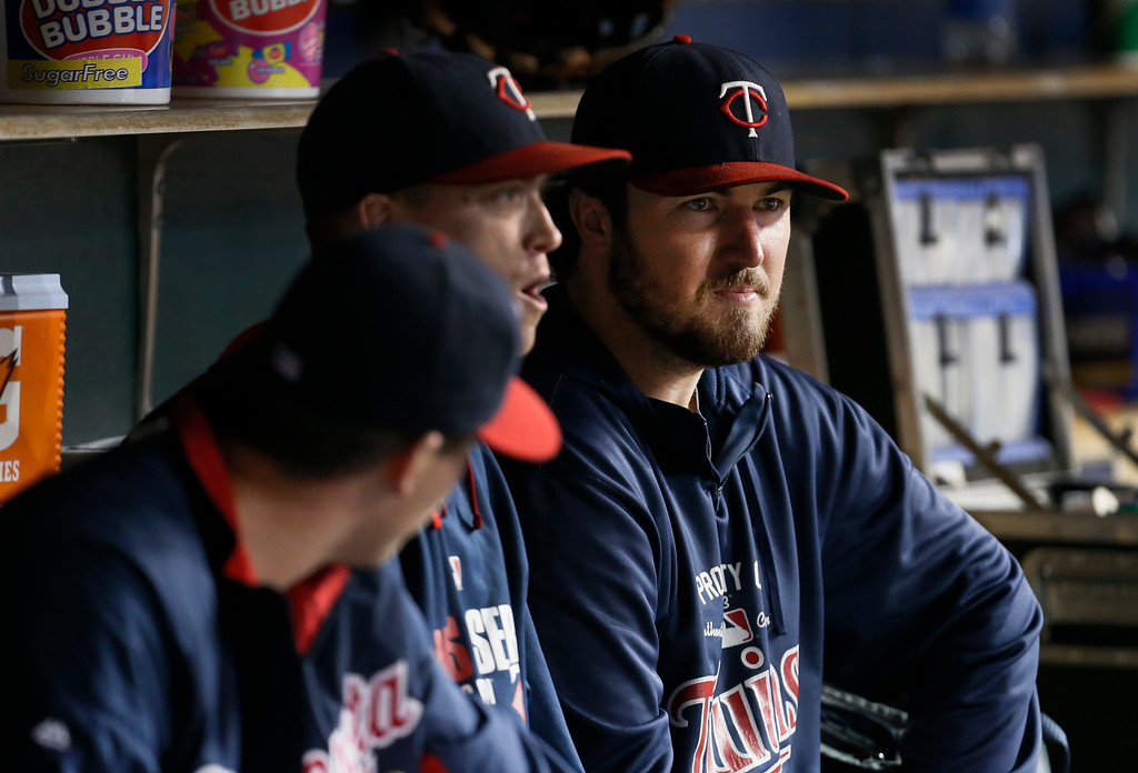 . Minnesota Twins pitcher Phil Hughes, right, watches from the dugout in the the seventh inning of a baseball game against the Detroit Tigers in Detroit, Thursday, Sept. 25, 2014. Hughes turned down a chance to pitch again this weekend, even though one more out would have earned him a $500,000 bonus. (AP Photo/Paul Sancya)