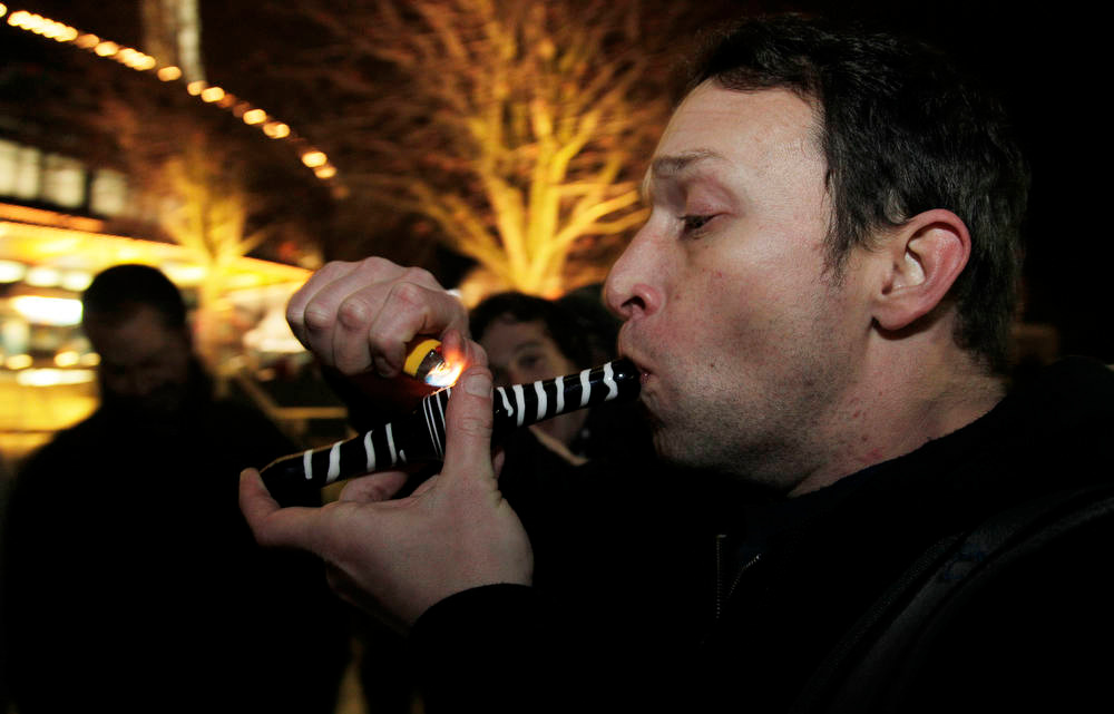 Description of . Gary Parrish smokes marijuana in a glass pipe, Thursday, Dec. 6, 2012, just after midnight at the Space Needle in Seattle. Possession of marijuana became legal in Washington state at midnight, and several hundred people gathered at the Space Needle to smoke and celebrate the occasion, even though the new law does prohibit public use of marijuana. (AP Photo/Ted S. Warren)