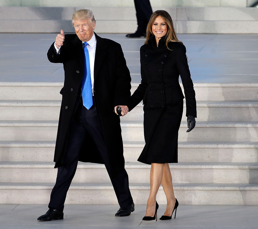 ". FILE - This Jan. 19, 2017 file photo shows President-elect Donald Trump and his wife Melania Trump wearing a black suit at a pre-Inaugural ""Make America Great Again! Welcome Celebration\"" at the Lincoln Memorial in Washington. Throughout the bruising presidential race, Mrs. Trump kept her look to typical wealthy socialite. Her blouses were often jewel toned, her dresses and jumpsuits from European designers that include Gucci and Roland Mouret, but Americans, too. (AP Photo/David J. Phillip)"