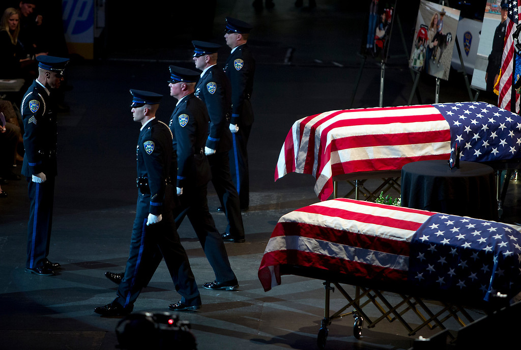 . American flags are draped over the caskets holding the bodies of detective Sgt. Loran \'Butch\' Baker and detective Elizabeth Butler. (Kevin Johnson/Sentinel)