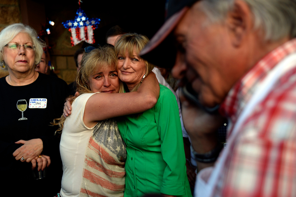 . Supporter Kandee Evans (American flag shirt) and Ali Betz hug as Tom Tancredo gives his concession speech during his Republican gubernatorial primary watch party. Tom Tancredo watch party on Tuesday, June 24, 2014. (Photo by AAron Ontiveroz/The Denver Post)