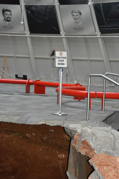 "Irony. ""Caution Step Down"" sign is meant for the steps to the right; however, now it serves another purpose.   Permission given to use this image with credit to the National Corvette Museum"