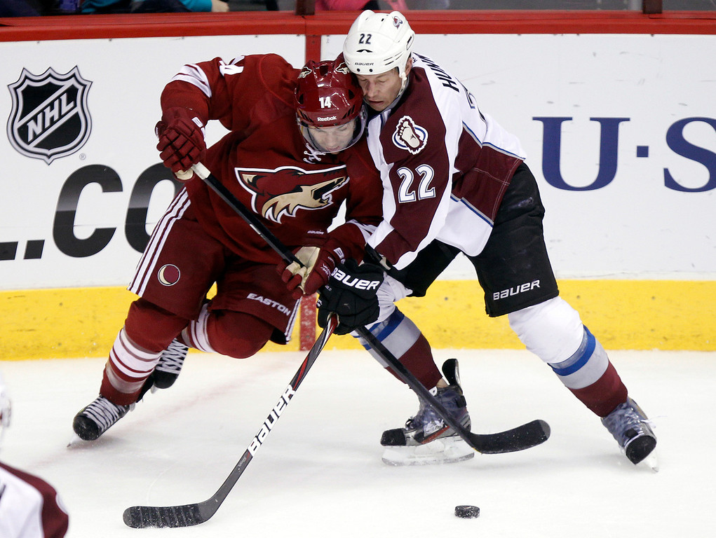 . Phoenix Coyotes right winger Chris Conner, left, battles Colorado Avalanche defenseman Matt Hunwick, right, for the puck in the second period of NHL hockey game, Saturday, April 6, 2013, in Glendale, Ariz. (AP Photo/Paul Connors)
