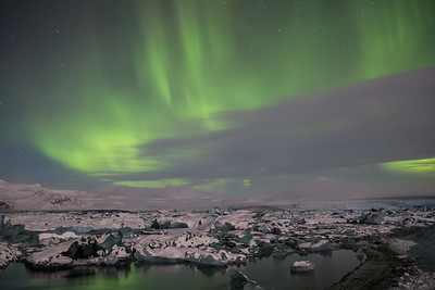 Aurora above Jokulsarlon glacier lagoon.  Icebergs floating below the glow.