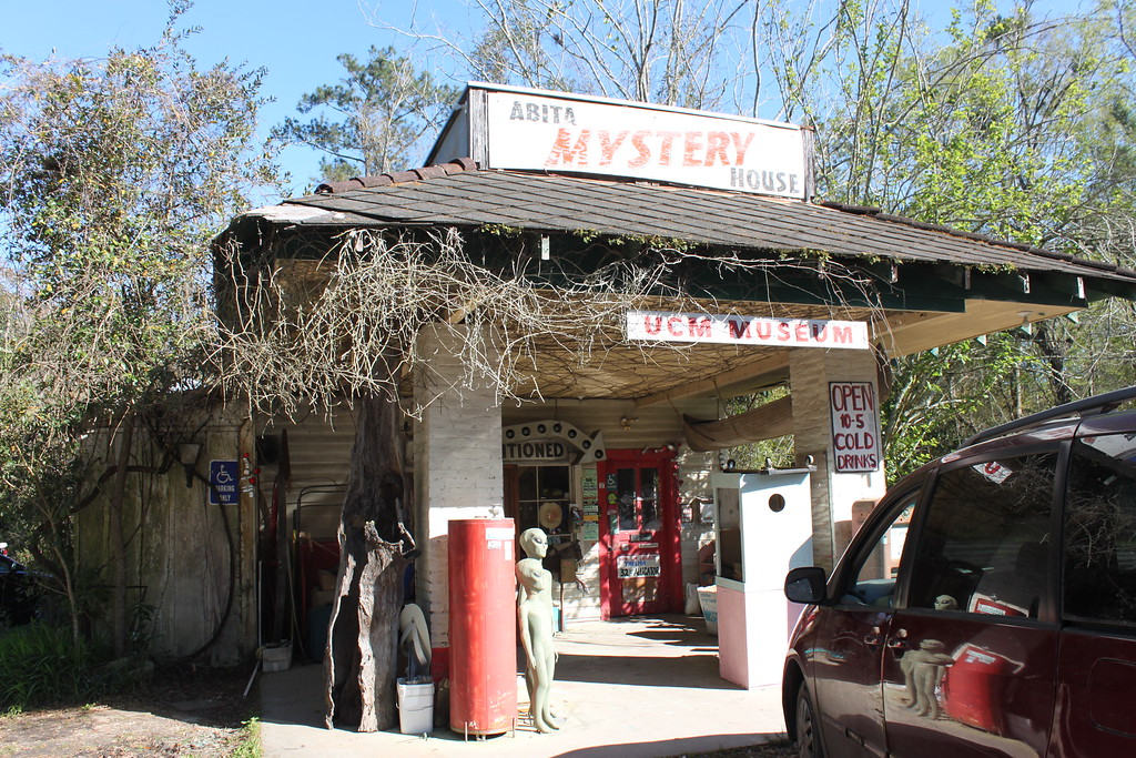 A former gas station is grown over with vines and has signs that say Abita Mystery House, UCM Museum, and Open 10-5 Cold Drinks next to an Alien statue