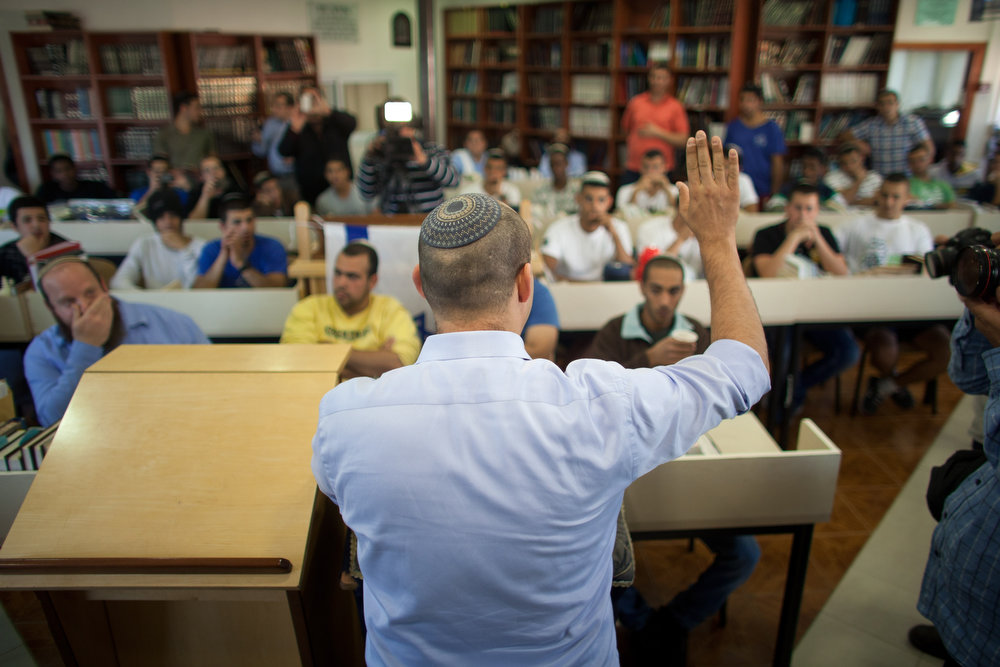 . Naftali Bennett  (L), head of HaBayit HaYehudi Party, the Jewish Home party, talks to students at a pre-army training school as he campaigns in the Shapira Center on January 20, 2013 near Ashkelon, Israel. The religious Jewish Home party is challenging Benjamin Netanyahu\'s Likud party as Israel heads for a general election on January 22.  (Photo by Uriel Sinai/Getty Images)