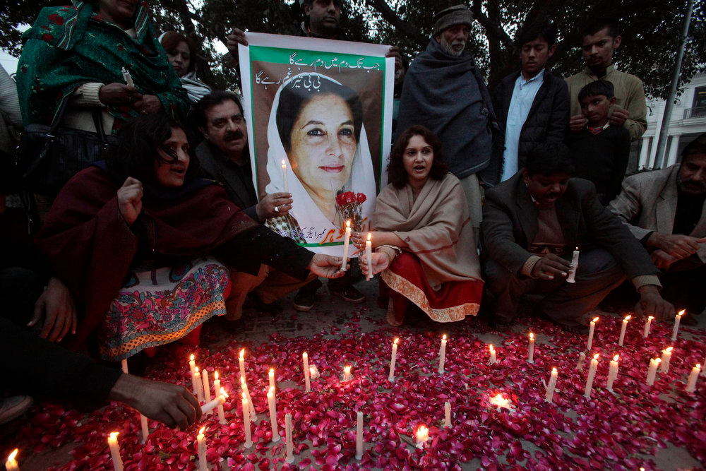Description of . Pakistan Peoples Party (PPP) supporters light candles beside a poster of Pakistan's former Prime Minister Benazir Bhutto during her death anniversary in Lahore December 27, 2012. Bhutto was killed in a gun and suicide bomb attack after an election rally in the city of Rawalpindi on December 27, 2007, weeks after she returned to Pakistan after years in self-imposed exile.  REUTERS/Mohsin Raza