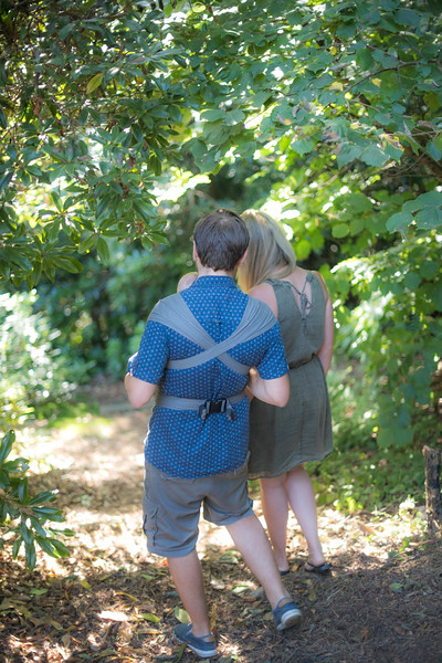 Izmi_Baby_Carrier_Breeze_Mid_Grey_Lifestyle_Front_Facing_Carry_Mum_And_Dad_Walking_In_Woods_Back_View.jpg