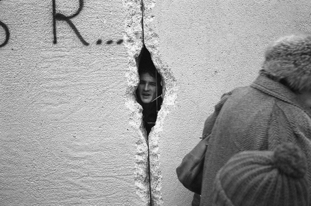 . A young man peers into East Berlin though a hole in the Berlin Wall at the effective end of the city\'s partition, 31st December 1989. (Photo by Steve Eason/Hulton Archive/Getty Images)