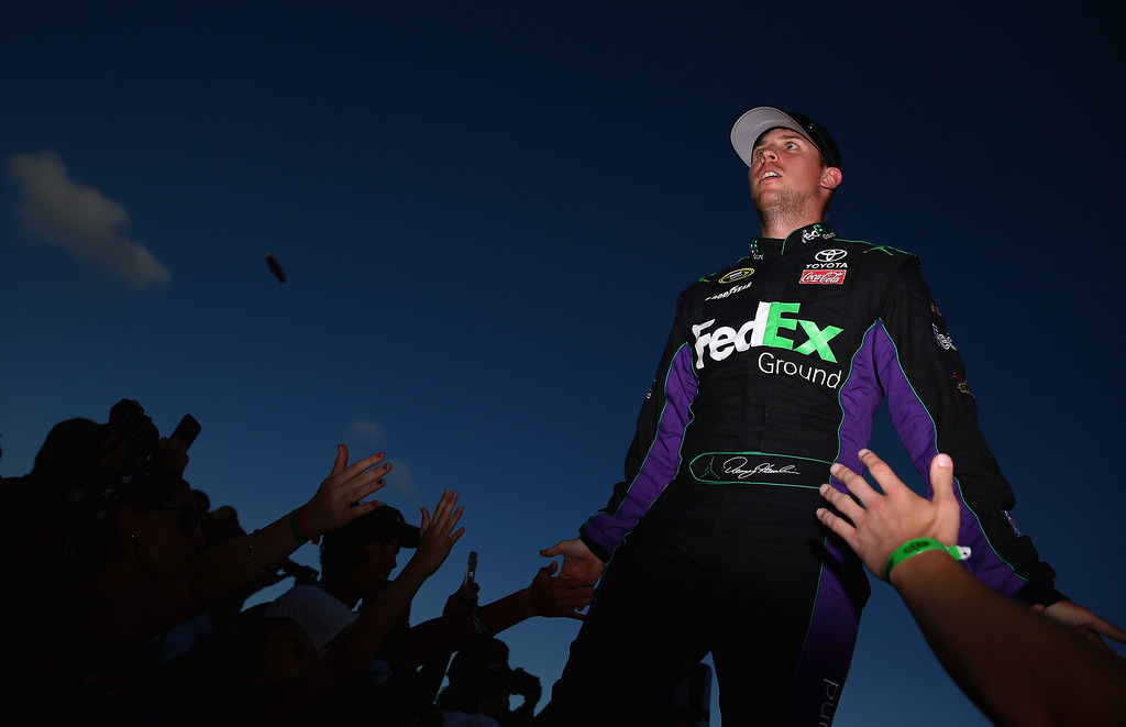 . DAYTONA BEACH, FL - JULY 06:  Denny Hamlin, driver of the #11 FedEx Ground Toyota, greets fans during driver introductions during the NASCAR Sprint Cup Series Coke Zero 400 at Daytona International Speedway on July 6, 2013 in Daytona Beach, Florida.  (Photo by Tom Pennington/Getty Images)