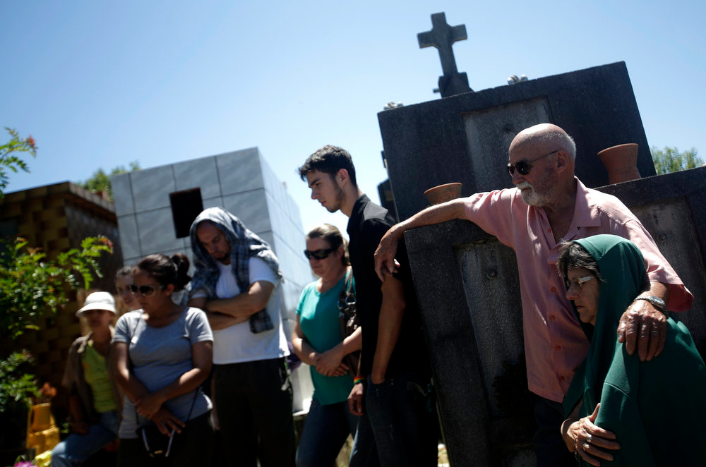 Description of . Relatives of Paula Simone Melo Prates, who died during the fire at Boate Kiss nightclub, attend her funeral at the cemetery in the southern city of Santa Maria, 187 miles (301 km) west of the state capital Porto Alegre, January 28, 2013. The nightclub fire killed at least 233 people in southern Brazil on Sunday when a band's pyrotechnics show set the building ablaze and fleeing partygoers stampeded toward blocked exits in the ensuing panic, officials said. REUTERS/Ricardo Moraes
