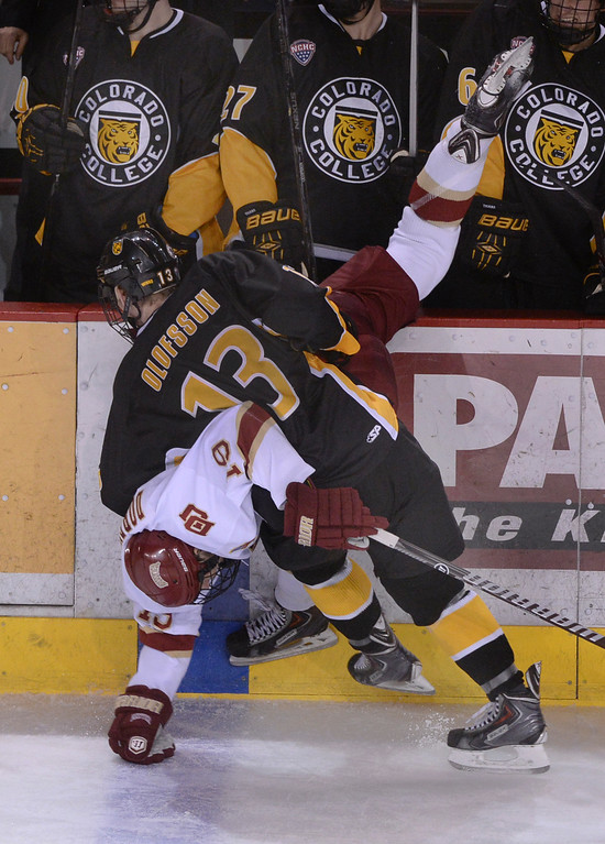 . DENVER, CO. - FEBRUARY 21, 2014: Tigers\' defenseman Gustav Olofsson (13) and Pioneers\' center Daniel Doremus (19) collided along the boards in the third period. The Colorado College hockey team defeated Denver 3-2 at Magness Arena Friday night, February 21, 2014. Photo By Karl Gehring/The Denver Post