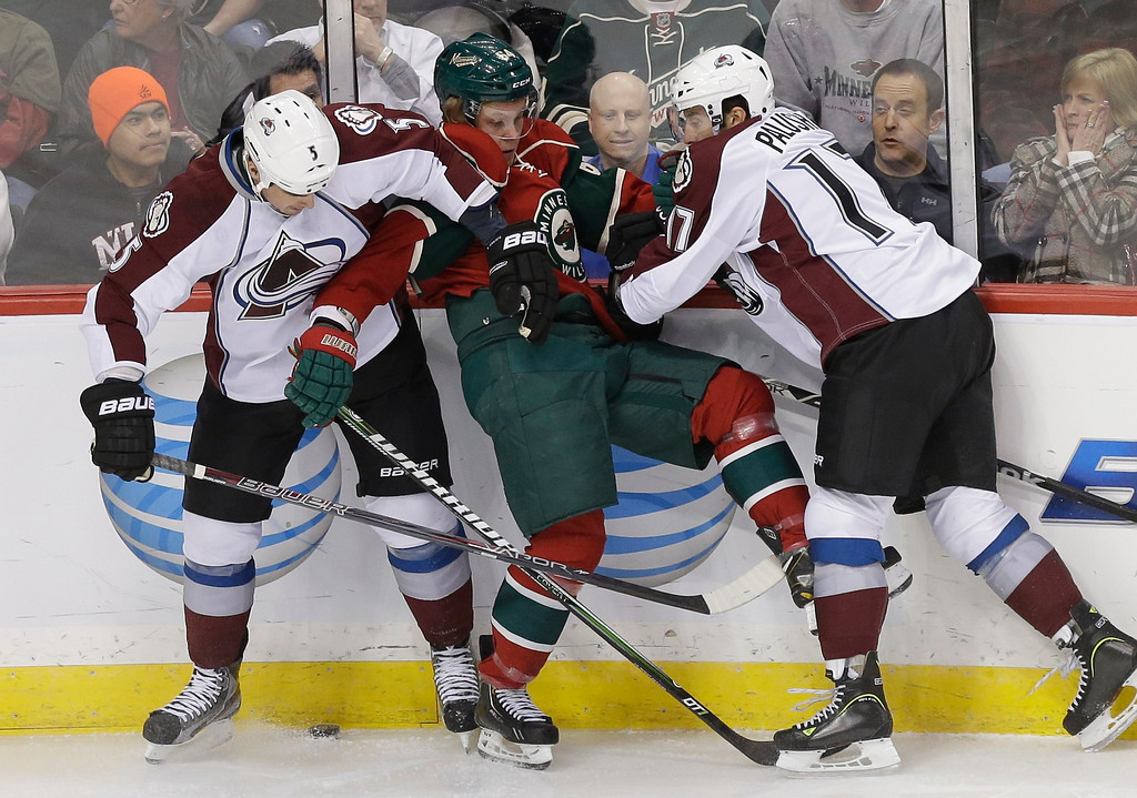 . Minnesota Wild\'s Mikael Granlund, center, of Finland, is squeezed between Colorado Avalanche\'s Shane O\'Brien, left, and Aaron Palushaj, right, in a battle for the puck in the first period of an NHL hockey game on Thursday, Feb. 14, 2013, in St. Paul, Minn. (AP Photo/Jim Mone)