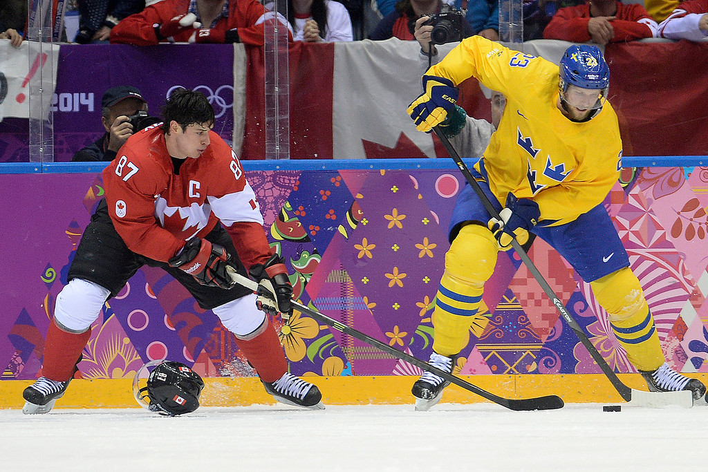 . Sidney Crosby (87) of Canada plays without a helmet as Alexander Edler (23) of Sweden controls the puck during the second period of the men\'s ice hockey gold medal game. Sochi 2014 Winter Olympics on Sunday, February 23, 2014 at Bolshoy Ice Arena. (Photo by AAron Ontiveroz/ The Denver Post)