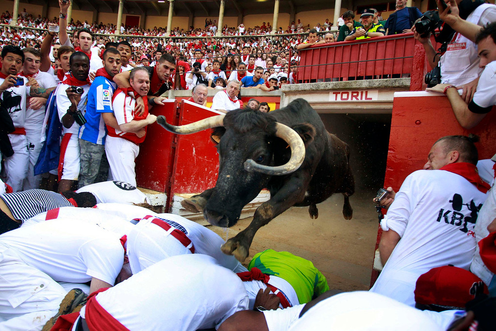 . A fighting cow leaps over revelers into the bull ring after the fourth running of the bulls at the San Fermin festival in Pamplona July 10, 2013. REUTERS/Joseba Etxaburu