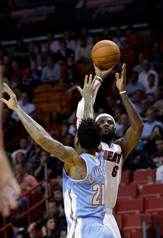 . Miami Heat forward LeBron James (6) prepares to shoot as Denver Nuggets forward Wilson Chandler (21) defends during the first  half of an NBA basketball game in Miami, Friday, March 14, 2014. (AP Photo/Alan Diaz)