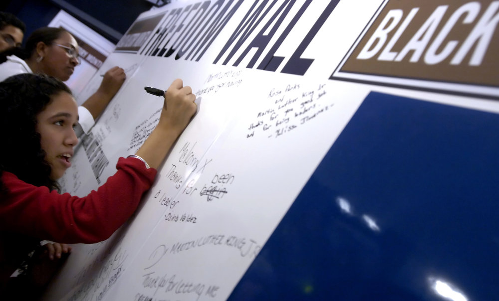 Description of . Cynthya Reyes, 14, of Manhattan, signs the Freedom Wall as she visits an exhibit celebrating Martin Luther King, Jr. and the upcoming Black History Month at Madame Tussaud's Thursday, Jan. 12, 2006 in New York.  Dozens of area middle school students visited the exhibit which included wax figures of Martin Luther King, Jr., Malcolm X, Nelson Mandela, Rosa Parks and nine other prominent African Americans as well as the Freedom Wall on which the students wrote messages honoring their heroes.  (AP Photo/Jason DeCrow)