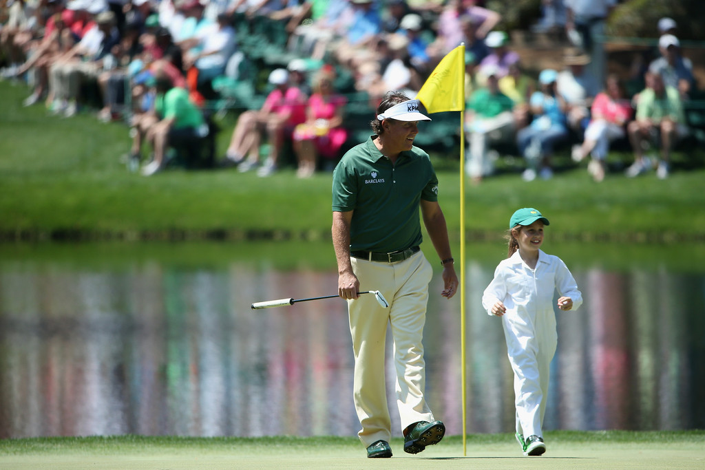 . Phil Mickelson of the United States walks across the ninth green with Emma Mackay during the Par 3 Contest prior to the start of the 2014 Masters Tournament at Augusta National Golf Club on April 9, 2014 in Augusta, Georgia.  (Photo by Andrew Redington/Getty Images)