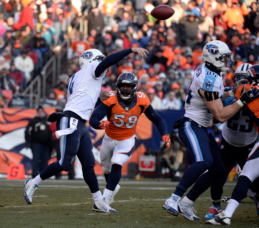 . Tennessee Titans quarterback Ryan Fitzpatrick (4) sends the ball down field as Denver Broncos outside linebacker Von Miller (58) comes in.  (Photo by Tim Rasmussen/The Denver Post)