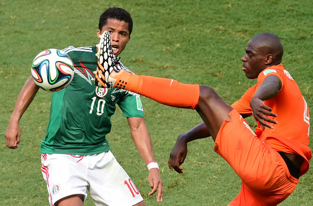 . Mexico\'s forward Giovani Dos Santos (L) and Netherlands\' defender Bruno Martins Indi vie for the ball during a Round of 16 football match between Netherlands and Mexico at Castelao Stadium in Fortaleza during the 2014 FIFA World Cup on June 29, 2014. AFP PHOTO / JAVIER SORIANO