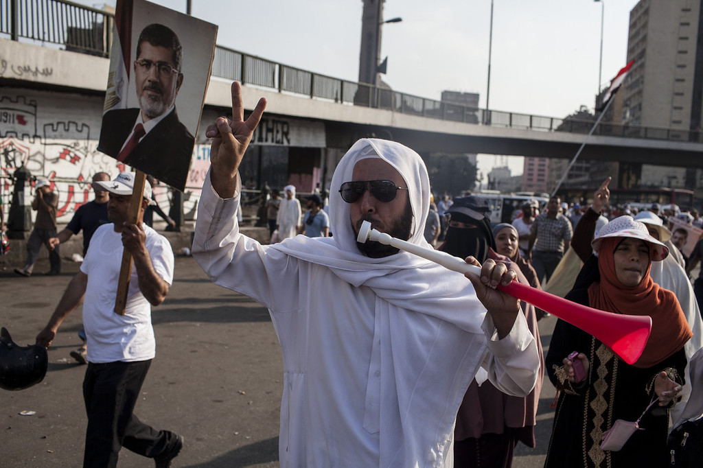 . A supporter of deposed Egyptian President Mohammed Morsi uses a vuvzela horn during a protest march in central Cairo on August 12, 2013 in Cairo, Egypt. Egyptian security forces threatened to begin a siege of pro-Morsi protest camps in Cairo overnight on August 11, however Egypt\'s Interior Ministry appeared to have put off plans to crack down on protesters early on August 12. On Monday Egypt\'s judiciary also extended deposed President Morsi\'s detention for a further 15 days pending investigation into charges of his collaboration with the Palestinian Hamas movement. Morsi supporters have continued to protest at sites across Cairo over one month after the Egyptian military deposed Egypt\'s first democratically elected President, Mohammed Morsi, on July 3. (Photo by Ed Giles/Getty Images).