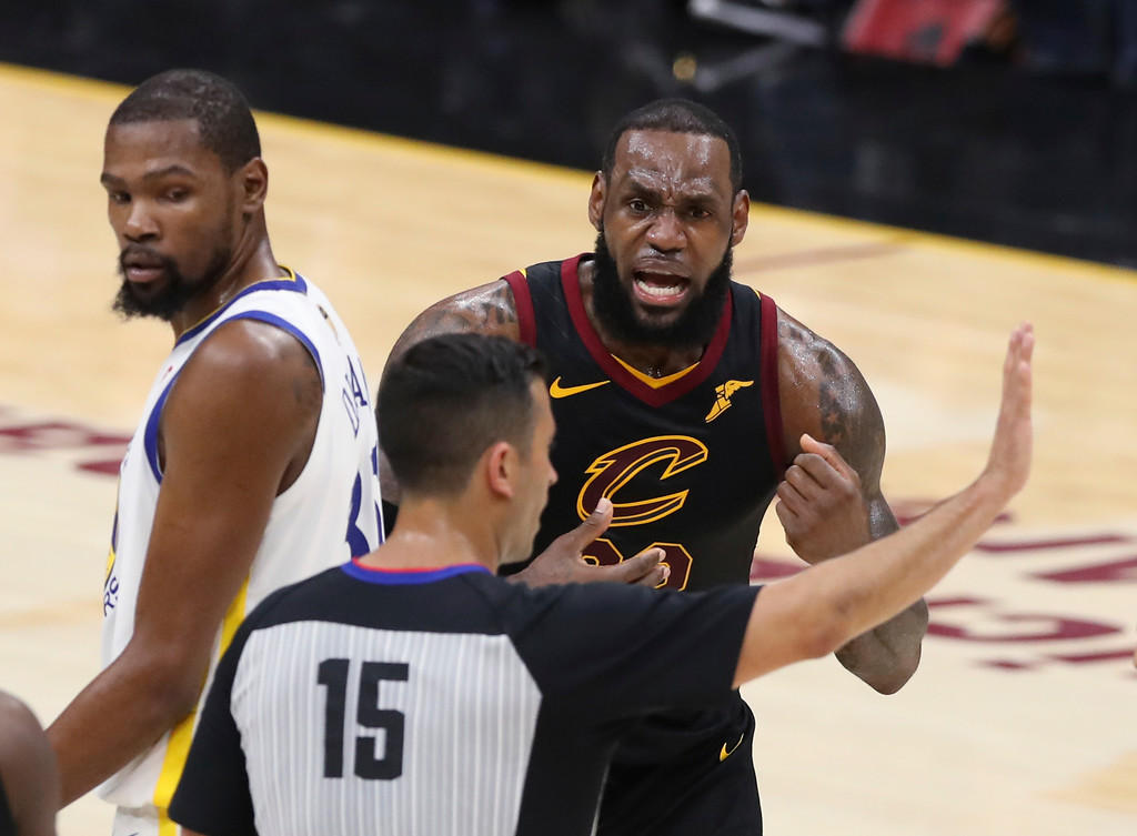 . Cleveland Cavaliers\' LeBron James argues a call with referee Zach Zarba (15) during the first half against the Golden State Warriors in Game 3 of basketball\'s NBA Finals, Wednesday, June 6, 2018, in Cleveland. Warriors\' Kevin Durant is at left. (AP Photo/Carlos Osorio)