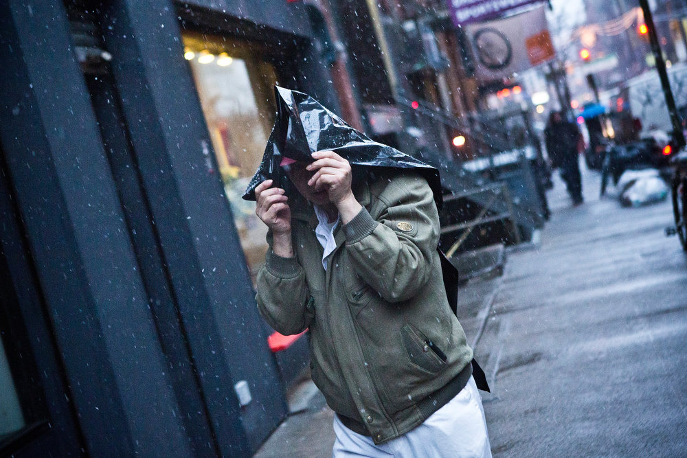 Description of . A man uses a plastic bag to protect himself from winter snow on December 26, 2012 in New York City. Snow, mixed with and changing to rain, is expected to hit the New York City area this afternoon into the evening. (Photo by Andrew Burton/Getty Images)
