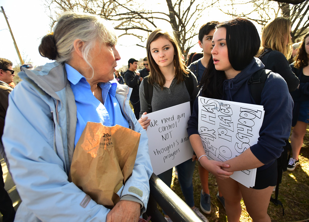. Kathleen Galt, left, gives encouragement to students Claire Mahon and Sophie Katz, at right, during a walkout to protest gun violence at Boulder High School on Wednesday morning.  For more photos go to dailycamera.com Paul Aiken Staff Photographer March 14, 2018.