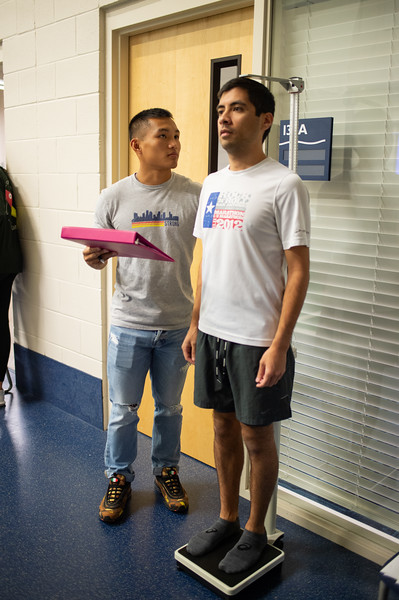 Christian Stauig (left) measures student James Rodriguez Height and weight before undergoing a various set of fitness tests for their kinesiology lab.