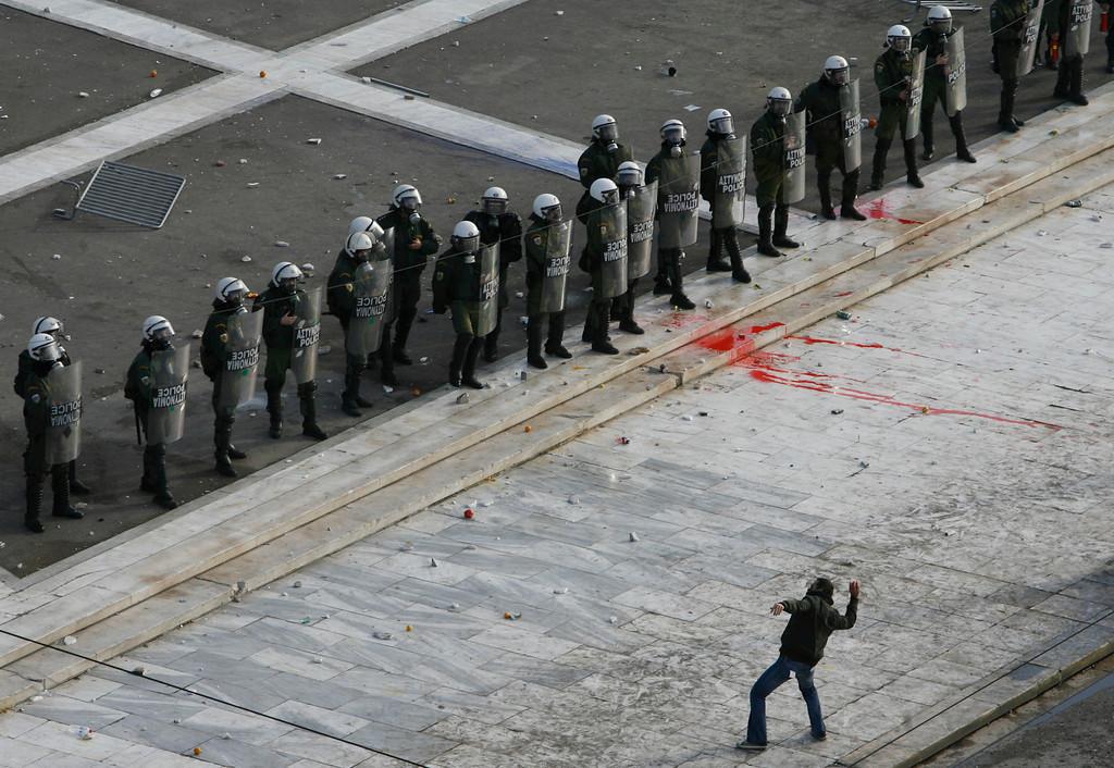 . A protester throws a stone at police in front of the Greek Parliament building during clashes in Athens, December 12, 2008. Greek students hurled firebombs and stones at police outside parliament in violence over the police killing of a teenager that has threatened Greece\'s government.   REUTERS/John Kolesidis