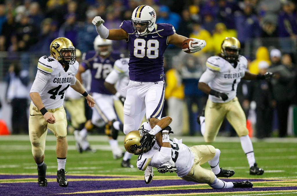 . Washington tight end Austin Seferian-Jenkins (88) is tackled by the leg by Colorado defensive back Greg Henderson, bottom, as Colorado\'s Addison Gillam (44) looks on in the first half of an NCAA college football game on Saturday, Nov. 9, 2013, in Seattle. (AP Photo/Ted S. Warren)