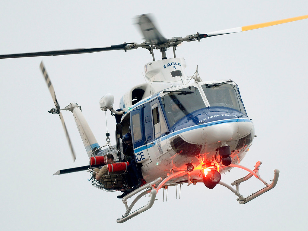 . A U.S. Park Police helicopter with a person in the rescue basket, flies over a building at the Washington Navy Yard in Washington, Monday, Sept. 16, 2013. At least one gunman opened fire inside a building at the Washington Navy Yard on Monday morning. (AP Photo/Susan Walsh)