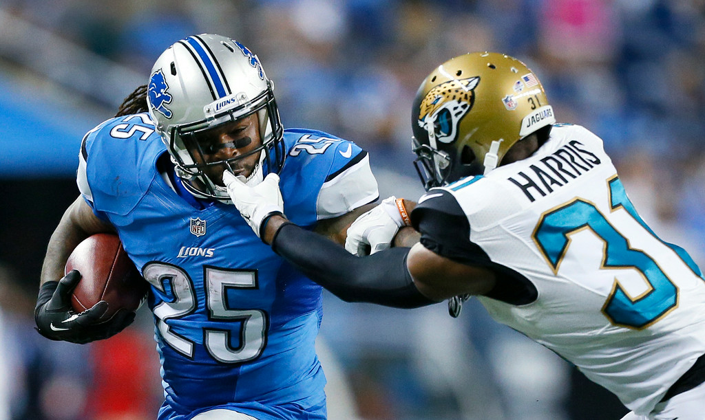 . Jacksonville Jaguars cornerback Jeremy Harris (31) grabs Detroit Lions running back Mikel Leshoure\'s (25) face mask in the second half of a preseason NFL football game at Ford Field in Detroit, Friday, Aug. 22, 2014. (AP Photo/Rick Osentoski)