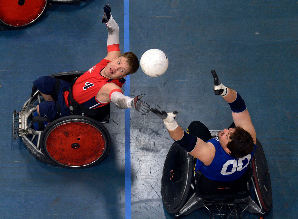 . DENVER, CO. - FEBRUARY 10: Adam Scaturro (4) of the Denver Harlequins (L) and Dave Nicholls (10) of the Northridge Knights reach out for the ball during the Wheelchair Rugby Tournament February 10, 2013 at Englewood High School.  The Mile High Mayhem was put on by Craig Hospital and city of Englewood.(Photo By John Leyba/The Denver Post)