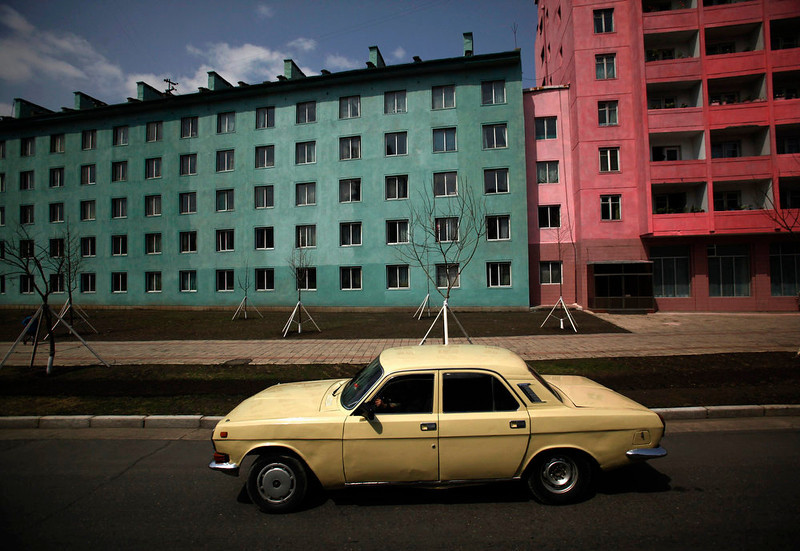 . A car drives past residential buildings in Pyongyang, on April 11, 2012. Chinese currency and U.S. dollars are being used more widely than ever in North Korea instead of the country\'s own money. The use of dollars and Chinese yuan, or renminbi, has accelerated since a revaluation of the North Korean won in 2009 wiped out the savings of millions of people, said experts on the country, defectors and Chinese border traders.   REUTERS/Bobby Yip/Files