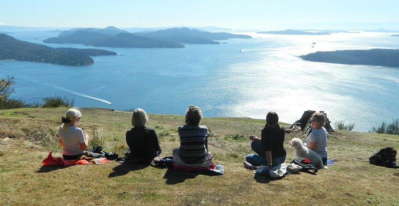 Women sitting on a hill overlooking the southern Gulf Islands in British Columbia.