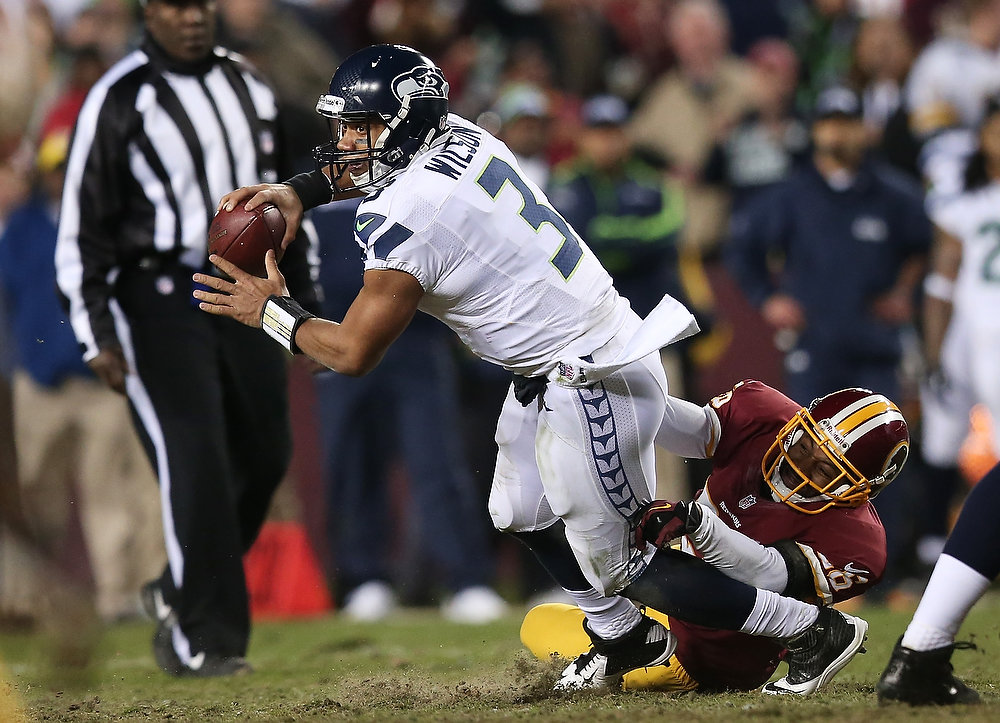 Description of . Russell Wilson #3 of the Seattle Seahawks is sacked by  Josh Wilson #26 of the Washington Redskins in the third quarter during the NFC Wild Card Playoff Game at FedExField on January 6, 2013 in Landover, Maryland.  (Photo by Win McNamee/Getty Images)
