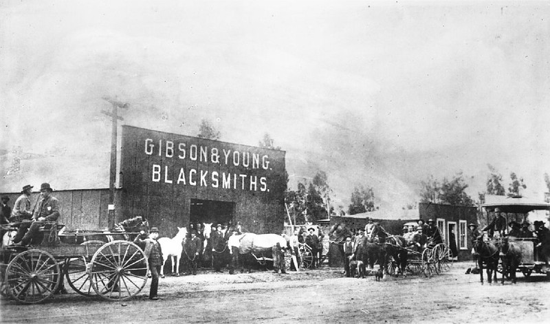 Horses and carriages gathered outside the Gibson and Young blacksmith shop, ca.1885