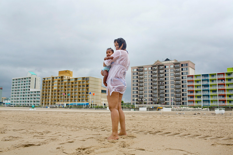 . Daisy de King of the Dominican Republic embraces her eight-month-old daughter after a quick swim, Friday, July 4, 2014 in Virginia Beach, Va. The storm was expected to bring a lousy July Fourth beach day with it as it moved offshore of the northeast coast. Forecasters did predict a second landfall Saturday evening in New Brunswick and Nova Scotia in Canada. (AP Photo/The Virginian-Pilot, Rich-Joseph Facun)