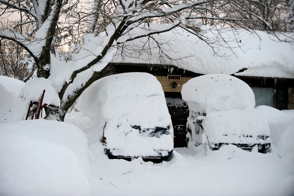 . Cars with snow atop the roofs sit idle at this home on Broadway in Lancaster,  N.Y. Wednesday, Nov. 19, 2014.  A ferocious storm dumped massive piles of snow on parts of upstate New York, trapping residents in their homes and stranding motorists on roadways, as temperatures in all 50 states fell to freezing or below.   (AP Photo/Gary Wiepert)