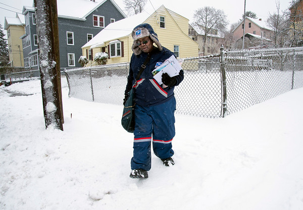 12/02/19 Wesley Bunnell | StaffrrA letter carrier makes her rounds through snow on Lawlor St. on Monday afternoon during the seasons first snow storm.