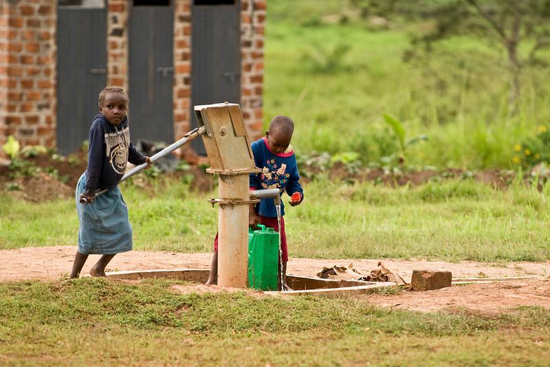children getting water in the village
