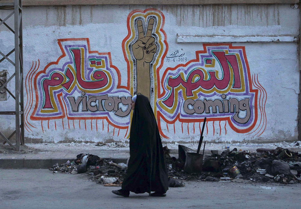 ". A woman walks along a street past graffiti that reads ""Victory coming\"" in Deir al-Zor April 20, 2013. Picture taken April 20, 2013. REUTERS/Khalil Ashawi"