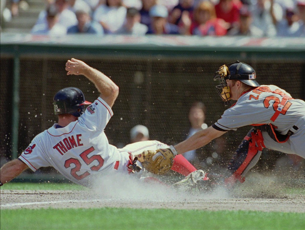 . Cleveland Indians runner Jim Thome (25) slides in to score under the tag from Baltimore Orioles catcher Gregg Zaun (24) on a sacrifice fly by Alvaro Espinoza in the second inning Saturday, Sept. 9, 1995, in Cleveland. Thome earlier tripled to drive in Dave Winfield. (AP Photo/Mark Duncan)