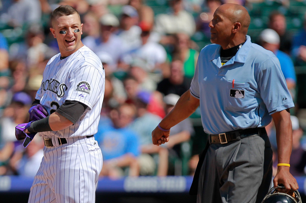 . Colorado Rockies\' Troy Tulowitzki talks with home plate umpire CB Buckner during the eighth inning of a baseball game against the San Diego Padres on Wednesday, Aug. 14, 2013, in Denver. The Rockies won 4-2. (AP Photo/Barry Gutierrez)