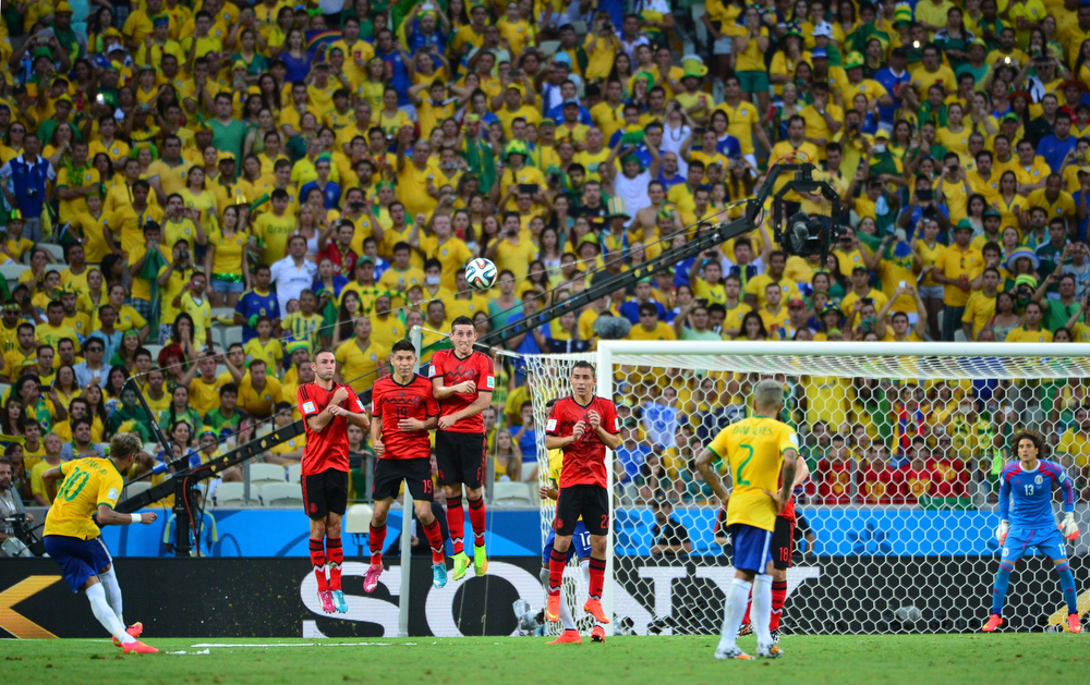 . Brazil\'s forward Neymar (L) kicks the ball during a Group A football match between Brazil and Mexico in the Castelao Stadium in Fortaleza during the 2014 FIFA World Cup on June 17, 2014.  (YURI CORTEZ/AFP/Getty Images)