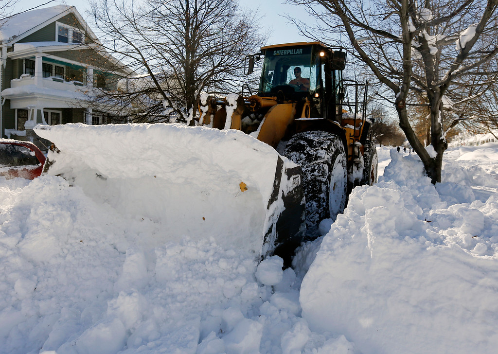. A front loader clears snow from a street in the south Buffalo on Friday, Nov. 21, 2014, in Buffalo, N.Y. A snowfall that brought huge drifts and closed roads in the Buffalo area finally ended Friday, yet residents still couldn\'t breathe easy, as the looming threat of rain and higher temperatures through the weekend and beyond raised the possibility of floods and more roofs collapsing under the heavy loads. (AP Photo/Mike Groll)