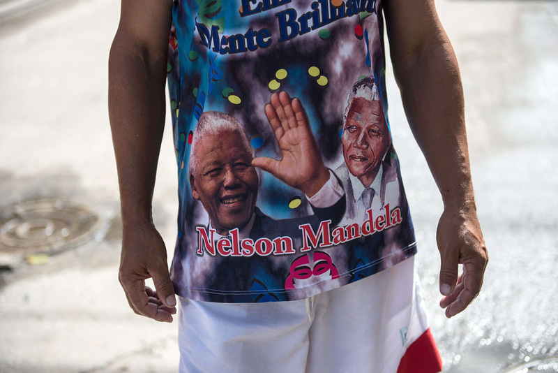 """. A man wears his carnival drum group \""""Batuqueiro do Nelson Mandela\"""" shirt at Mandela shantytown (favela) in Rio de Janeiro, Brazil, on December 6, 2013. The shantytown was named after Mandela to commemorate his discharge from prison in 1990. YASUYOSHI CHIBA/AFP/Getty Images"""